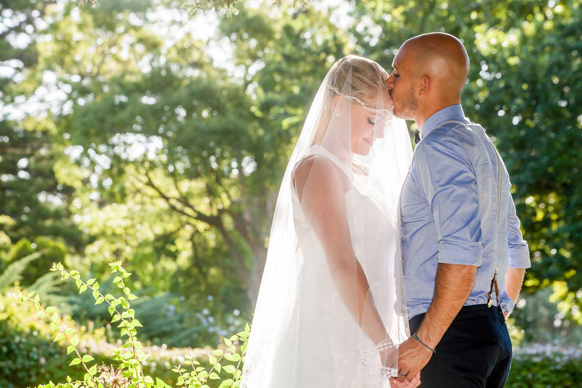groom kissing bride soft light