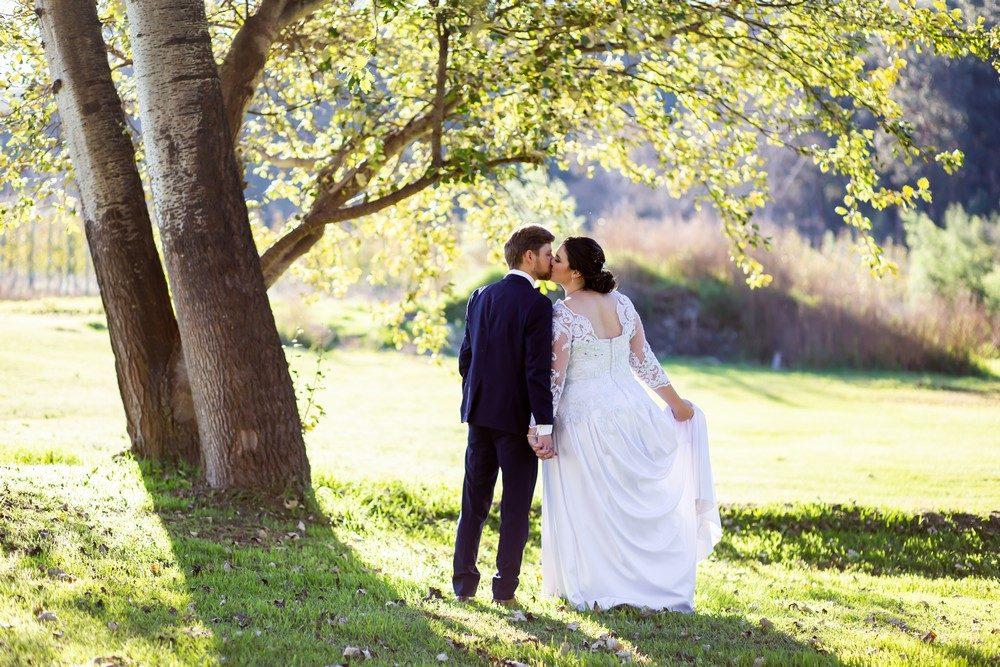 Houwhoek Hotel Wedding Bride and groom kissing under oak tree